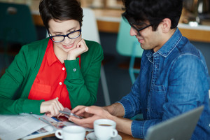 Portrait of two creative young people dressed in business casual smiling looking at smartphone while meeting at table in cafe