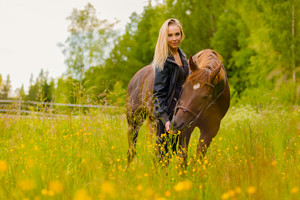 Portrait of woman feeding her arabian horse with snacks in the field