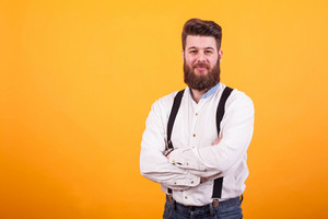 Portrait of young bearded man with arms crossed looking at the camera over yellow background. Attractive young man. Stylish beard.