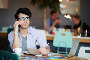 Portrait of young casual creative man calling by phone while sitting at table in cafe making notes