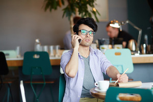 Portrait of young creative man calling by phone while making notes and working in cafe