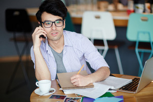 Portrait of young creative man wearing casual clothes and glasses sitting at table making notes while calling by phone and working with laptop in cafe