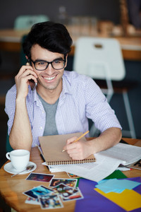 Portrait of young creative man wearing casual clothes and glasses sitting at table smiling and making notes while calling by phone