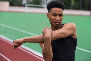 Portrait of young handsome african athlete man make stretching exercises on running track outdoors. Looking aside.
