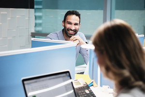Portrait of young happy successful male manager working in modern office. Busy hispanic business man smiling at work in executive coworking space with female colleague, looking at camera.