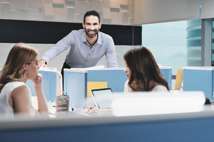 Portrait of young happy successful male manager working in modern office. Busy hispanic business man smiling at work in executive coworking space with female colleagues, looking at camera.
