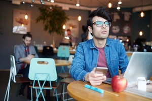 Portrait of young man wearing glasses and jeans jacket looking at away while working with laptop and smartphone at table in cafe