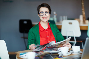 Portrait of young successful businesswoman wearing colorful casual clothes smiling cheerfully at camera while reading magazines at table