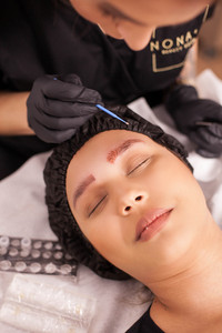Portrait of young woman after eyebrow tattoo removal in a beauty salon. Skin care. Caucasian woman. Modern treatment.