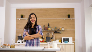 Portrait of young woman in her kitchen. Beautiful woman.