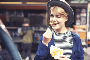 Portrait of young woman with fries winking