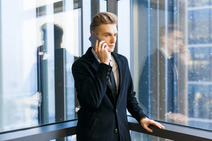 Portrait shot of serious white collar worker answering phone call while standing in office lobby with panoramic windows