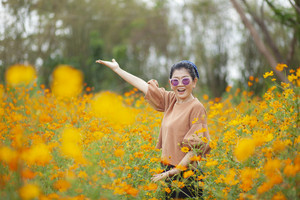 portrait smiling face asian woman standing with happiness emotion in yellow cosmos blooming field