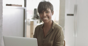 Portrait video of an attractive latina black student looking on ther smartphone screen and smiling