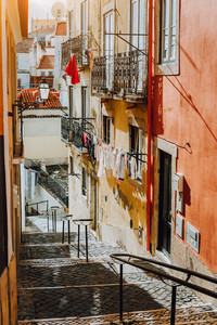 Portuguese old street. Hanging laundry at Sunset in the historical downtown of Lisbon, cityscape of Lissabon