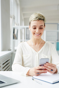 Positive young businesswoman choosing her favorite tracks from playlist in smartphone by workplace