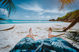 POV shot of man wear blue swimming shorts laying on a beautiful sandy tropical beach Anse Cosos, La Digue, Seychelles