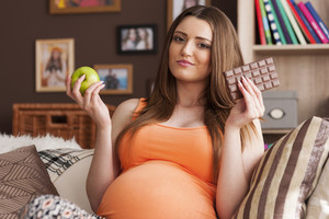 Pregnant woman considering the choice of healthy and unhealthy food