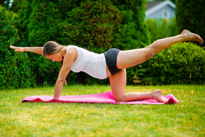 Pregnant Woman Doing Bird Dog Pose On Exercise Mat