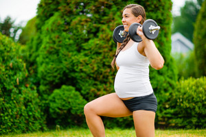 Pregnant Woman Doing Kneeling Lunges With Dumbbells In Park