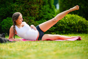 Pregnant Woman Performing Side Reclining Leg Lift In Park
