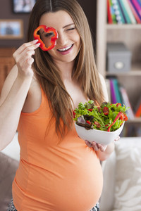 Pregnant woman with healthy salad at home