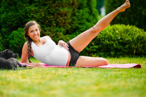 Pregnant Young Woman Performing Side Reclining Leg Lift In Park