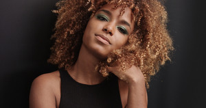 Pretty black girl with big hair posing video on black background