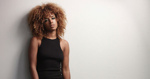 Pretty black girl with big hair posing video. on grey background