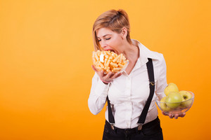 Pretty blond woman with short hair taking a bite from her corn puffs over yellow background. Tasty corn puffs,. Fresh apples. Green apples.