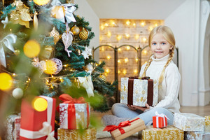 Pretty child with packed xmas present sitting by decorated firtree
