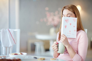 Pretty female hiding her face behind paper greeting-card made up by her child
