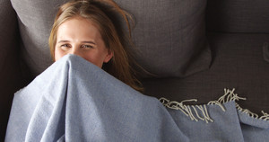 Pretty female model playing peekaboo with a light blue thin blanket lying on a dark grey couch