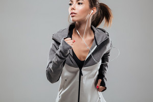Pretty female runner in warm clothes running in studio and looking away over gray background