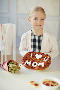 Pretty girl holding baked pie for her mom
