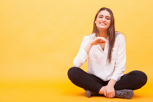Pretty girl smiling at the camera in studio and sitting down over yellow background. No worries