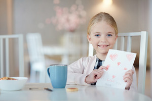 Pretty girl with greeting card looking at camera