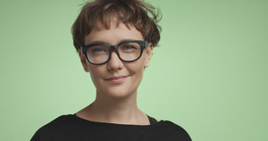 Pretty joyful smiling young woman with dark short hair wearing a black top and glasses isolated on color backgrounds