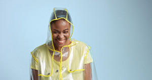 pretty mixed race woman with short hair in transparent raincoat