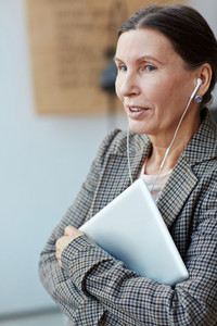 Pretty senior woman with laptop in hands looking away dreamily and listening to music with headphones, waist-up portrait