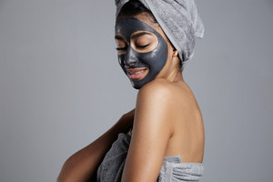 pretty smiling woman with a facial mask on