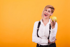 Pretty woman in white shirt laughing at her green apple over yellow background. Delicious fruit. Taking care of her health.