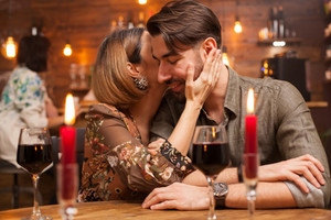 Pretty young couple making each other laugh in a vintage restaurant . Cadles burning. She's holding her arm on his right cheek. Two glasses of red wine