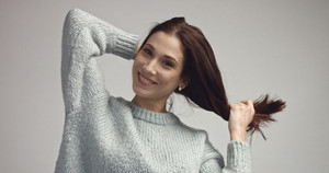 pretty young spanish woman posing in studia looking at camera and smiling wearing grey owersized sweater