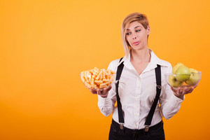 Pretty young woman looking at those delicious corn puffs over yellow background. Delicious green apples.