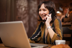 Pretty young woman smiling while talking on the phone and using her laptop in a coffee shop. Modern device. Breakfast