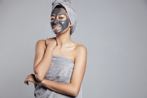 pretty young woman with facial coal black mask