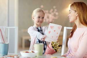 Pretty youngster giving handmade greeting-card to her mom