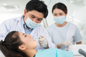 Professional team of a dentist and his assistant performing a dental procedure