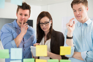 Professionals Planning Strategies On Adhesive Notes In Office